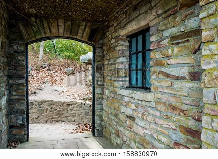 Arched stone entry beside constructed wall, path to outdoors