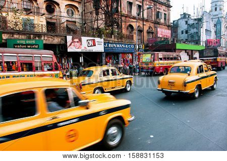 KOLKATA, INDIA - JAN 19, 2013: Yellow taxi cabs drive over speed limit on the street blurred in motion on January 19, 2013 in Kolkata, India. Kolkata has a density of 814.80 vehicles per km road length