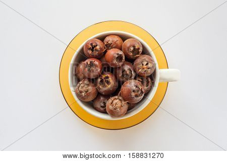 white bowl on a yellow saucer full of sweet medlar on a white background