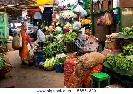 KOLKATA, INDIA - JANUARY 10, 2013: Vegetable seller reads a newspaper and waits for the customers on the old city market on January 10, 2013 in Calcutta. 0.81 perc. of Kolkata's workforce employed in agriculture