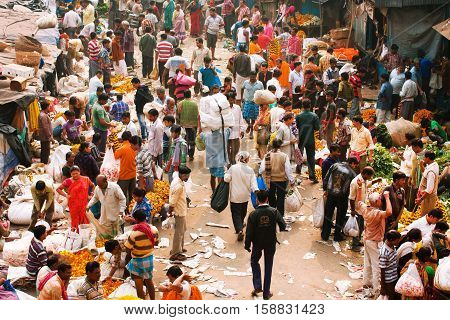 KOLKATA, INDIA - Feb 11, 2013: Big crowd of moving people on the Mullik Ghat Flower Market on February 11, 2013. The market is more than 125 years old. More than 2000 sellers work in the market every day