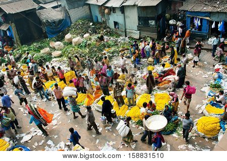 KOLKATA, INDIA - Feb 11, 2013: View of Mullik Ghat Flower Market with people scurrying around on February 11, 2013. The market is more than 125 years old. More than 2000 sellers work in the market every day