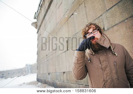 A bearded young man covers the frozen nose with a gloved hand on a cold winter day