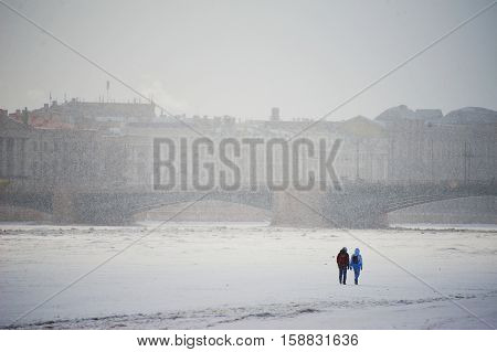 Two people walk on ice of Neva river in winter in the background through the fog the bridge is visible and the architectural ensemble of the St. Petersburg waterfront.