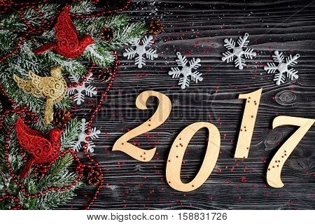 Christmas decorations, spruce branches on dark wooden background top view - 2017