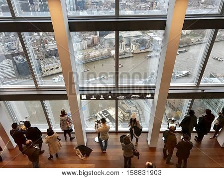 LONDON - NOVEMBER 27: Tourists look out over The River Thames and City of London from the observation gallery on the 69th floor of The Shard on November 27, 2016 in London, UK.