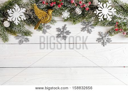 Christmas toys and spruce branches on wooden background top view.