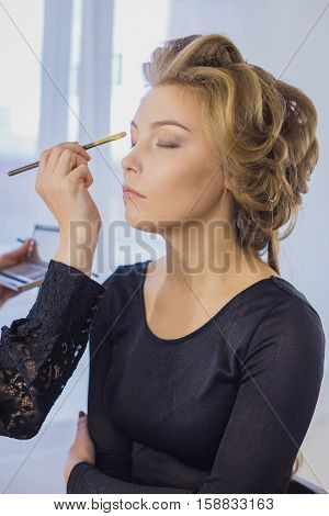 Close up shot. Professional make-up artist applies eye shadow to eyelid of model in white room. Beauty, makeup and fashion concept