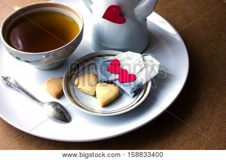 tea bags with hearts. tea, cookies on a white plate. plywood background