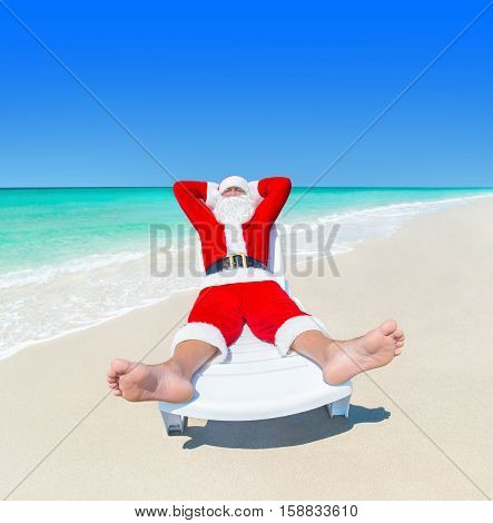 Christmas Santa Claus relax on sunlounger at tropical ocean sandy beach heels at foreground - New Year travel vacation in hot countries concept