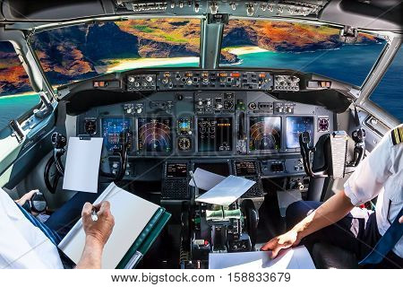 Airplane cockpit flying on Na Pali coast, Kauai, Hawaii, United States, with pilots arms and blank white papers for copy space.