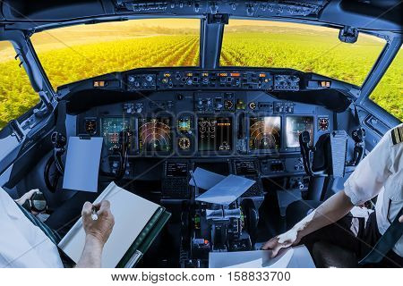 Airplane cockpit flying on Napa Valley at sunset, California, United States, with pilots arms and blank white papers for copy space.