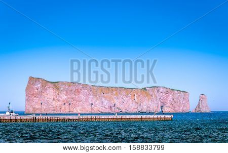 scenic view of Perce Rock in Gaspe Peninsula in St Lawrence river under a blue sky Quebec Canada