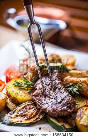 Beef Steak. Sirloin steak. Delicious juicy beef steak on fork. grill vegetables.