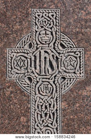 """Close up if engraved Celtic Cross with Christogram """"IHS"""" on gravestone"""