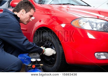Handsome mechanic inspecting the tire pressure in auto repair shop.