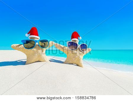 Sea stars couple (starfishes) in red Santa hats at turquoise ocean sandy beach. Merry Christmas and Happy New Year's Day travel destinations concept.