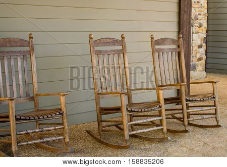 Rocking Chairs on home concrete porch with slatted wall and stone pillar