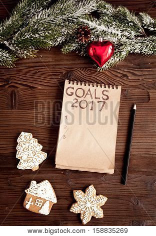 notebook and goals for new 2017 year on dark wooden background top view