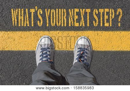 What`s your next step? print with sneakers on asphalt road top view.