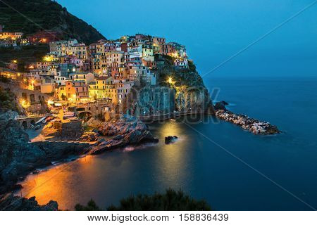 Manarola, Liguria, Italy. The wonderful Manarola village as you can see it from the mountain above. Quiet sky and peaceful sea, during sunset.