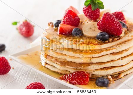 Pancakes with berries and maple syrup, close-up.