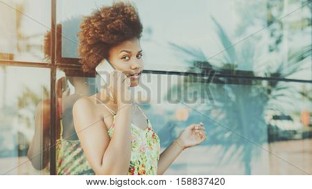 Black beautiful attractive young brazilian teen girl with curly hair in dress talking on smartphone standing in front of tiled glass wall with reflections of palms and cars sunny summer day