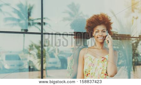 Black beautiful attractive young brazilian teen girl with curly hair in dress smiling while talking on smartphone standing in front of tiled glass wall with reflections of palms and cars sunny day