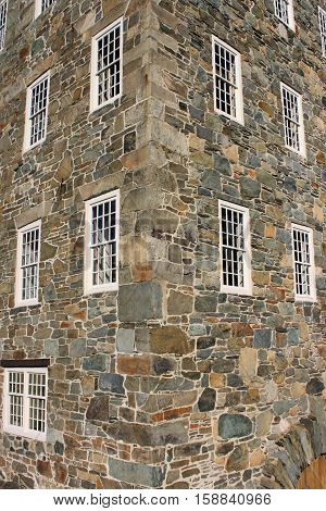 Corner stones of an 18th century factory showing twelve over twelve window panes.