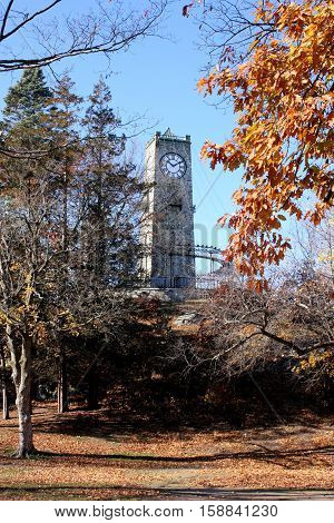 19th century stone clock tower built on a rocky outcropping on a  sunny autumn day.