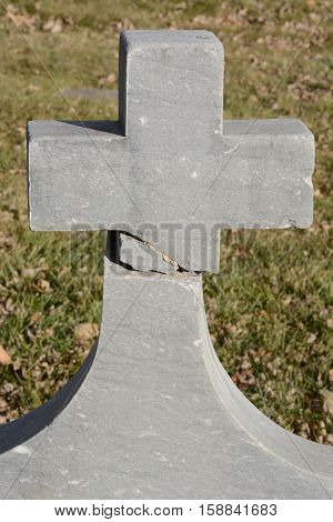 Broken and repaired Christian cross old granite gravestone