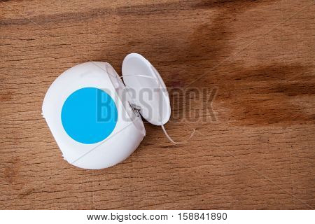 Dental floss isolated on wood desk. Dental care