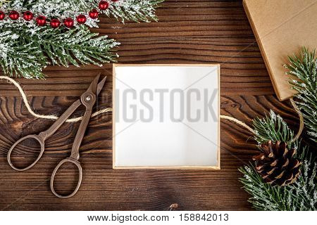 packaging christmas gifts in boxes on dark wooden background top view.