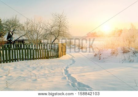 Winter rural landscape in nice weather- winter house among frosty trees and winter nature at sunset.Sunny view of picturesque winter countryside nature. Winter landscape scene lit by soft sunset light