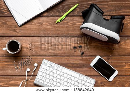 virtual reality glasses with blank open notebook on mans working wooden desktop top view