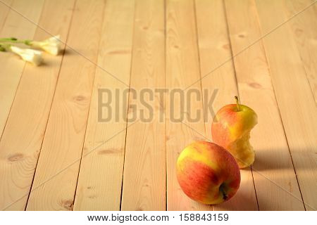 Apple and flower on wood table at the morning.
