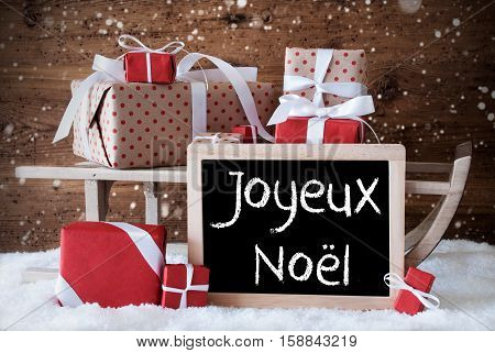 Chalkboard With French Text Joyeux Noel Means Merry Christmas. Sled With Christmas And Winter Decoration And Snowflakes. Gifts And Presents On Snow With Wooden Background.