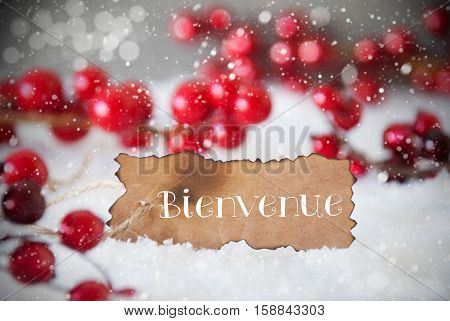 Burnt Label With French Text Bienvenue Means Welcome. Red Christmas Decoration On Snow. Cement Wall As Background With Bokeh Effect And Snowflakes. Card For Seasons Greetings