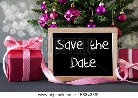 Chalkboard With English Text Save The Date. Christmas Tree With Rose Quartz Balls And Bokeh Effect. Gifts Or Presents In The Front Of Cement Background.