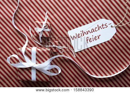Label With German Text Weihnachtsfeier Means Christmas Party. Two Gifts Or Presents With White Ribbon. Red And Brown Striped Wrapping Paper. Christmas Or Greeting Card.