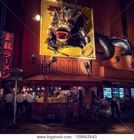 Osaka - July 2016: Night street view with dragon decoration above small bistro. Dotonbori
