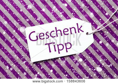 German Text Geschenk Tipp Means Gift Tip. One Label On A Purple Striped Wrapping Paper. Textured Background With Snowflakes. Tag With Ribbon.