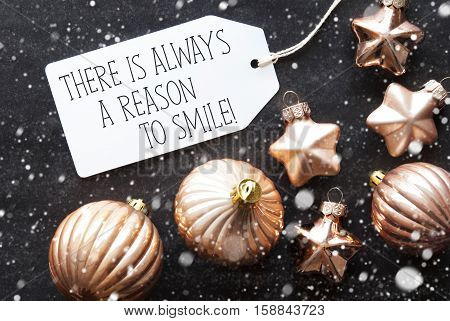 Label With English Quote There Is Always A Reason To Smile. Bronze Christmas Tree Balls On Black Paper Background With Snowflakes. Christmas Decoration Or Texture. Flat Lay View
