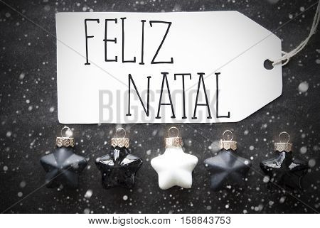 Label With Portuguese Text Feliz Natal Means Merry Christmas. Black And White Christmas Tree Balls On Black Paper Background With Snowflakes. Christmas Decoration Or Texture. Flat Lay View