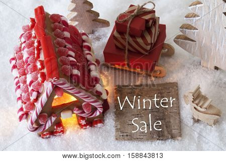 Label With English Text Winter Sale. Gingerbread House On Snow With Christmas Decoration Like Trees And Moose. Sleigh With Christmas Gifts Or Presents.