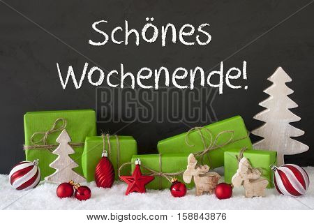 German Text Schoenes Wochenende Means Happy Weekend. Green Gifts Or Presents With Christmas Decoration Like Tree, Moose Or Red Christmas Tree Ball. Black Cement Wall As Background With Snow.