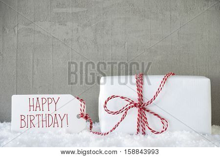 One Christmas Gift Or Present On Snow With Red Ribbon. Cement Or Concrete Wall As Background. Modern And Urban Style. Card For Birthday Or Seasons Greetings. Label With English Text Happy Birthday