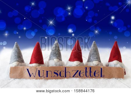 Label With German Text Wunschzettel Means Wish List. Christmas Greeting Card With Gnomes. Sparkling Bokeh And Blue Background With Snow And Stars.