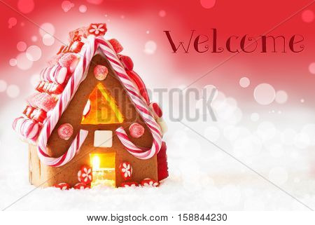 Gingerbread House In Snowy Scenery As Christmas Decoration. Candlelight For Romantic Atmosphere. Red Background With Bokeh Effect. English Text Welcome