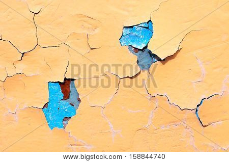 Texture background of light orange and turquoise peeling paint on the old rough texture surface - texture background with chipped grunge paint on the texture wall